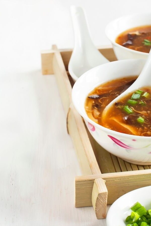 Keto Egg Drop Soup served in a white ceramic bowl on a bamboo platter