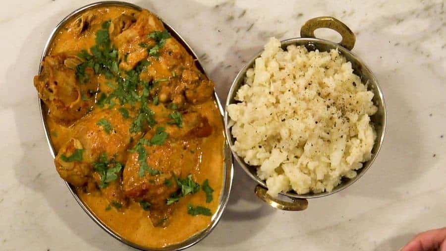 Overhead shot of finished butter chicken and steamed, mashed cauliflower.