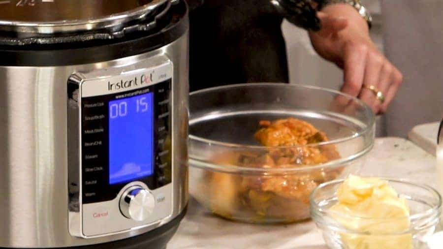 Side view of cooked chicken being removed from the Instant Pot. Sauce left behind.