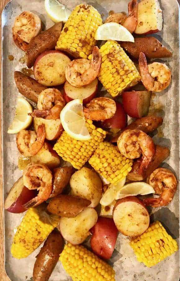 Instant Pot Cajun Shrimp Boil shows overhead view of potatoes, shrimp, corn, with spices and lemon on a large cookie sheet.