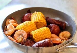 View of Corn, shrimp, and sausage in a saucepan. Fool-proof recipe for a perfectly cooked Cajun shrimp and sausage boil in your Instant Pot. Find out how to cook perfect shrimp in your pressure cooker.