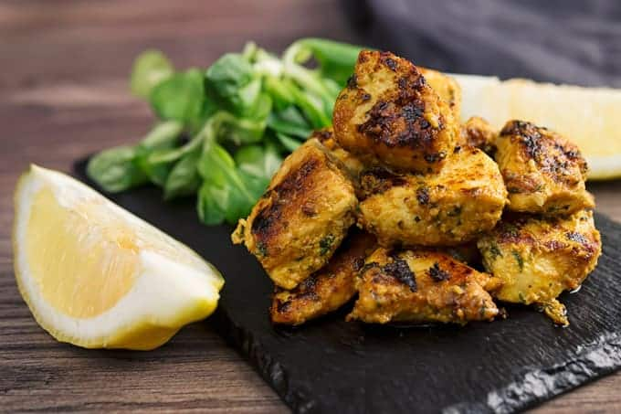 Chicken tikka bites on a black slate, with lemons and cilantro behind the chicken kababs