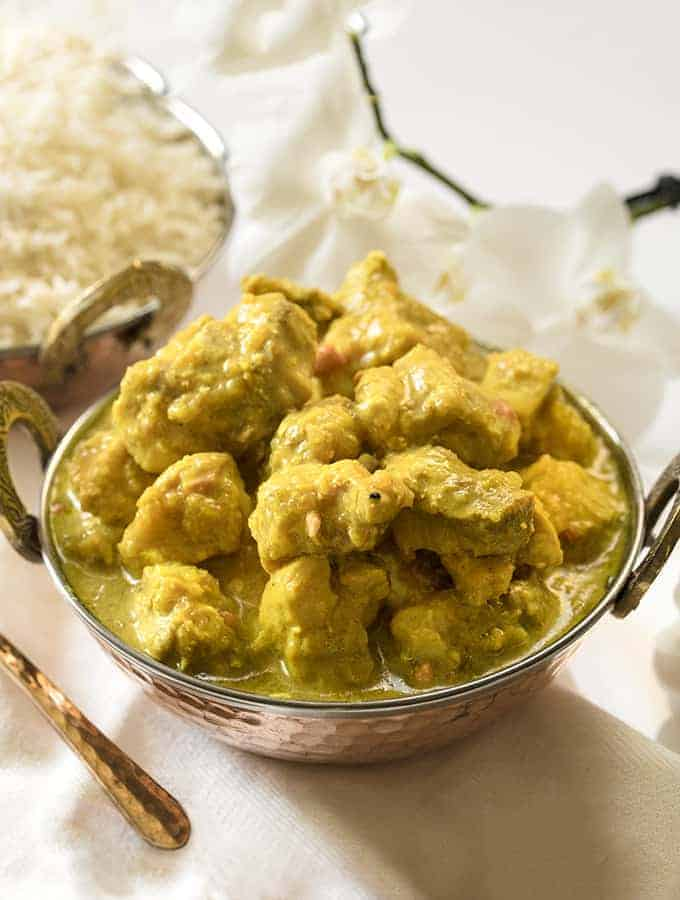 Instant pot chicken korma sideways view with rice in the background