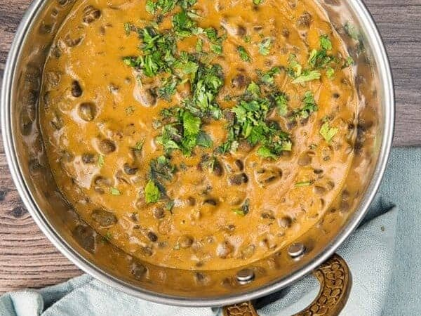 overhead view of dal makhani in a small brass wok