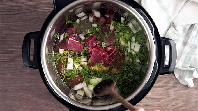 Overhead shot of the beef stew meat, water, onion, garlic, cilantro, ground cumin, and salt in the Instant Pot.