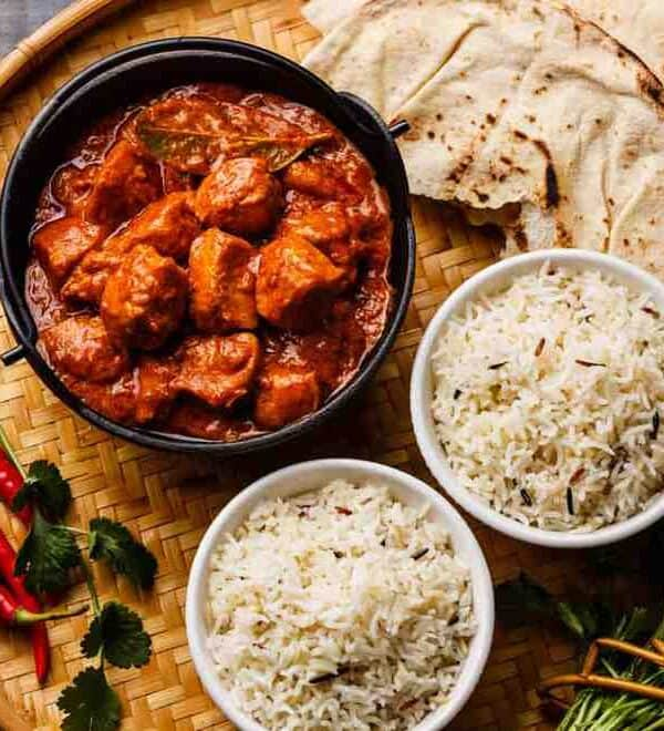 Chicken tikka masala spicy curry meat food in cast iron pot with rice and naan bread close up