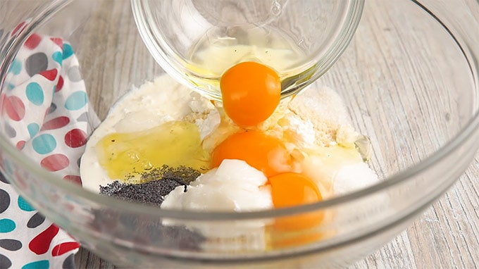 Eggs being poured into a bowl of ingredients for keto muffins