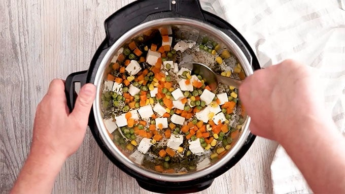 Ingredients for Paneer Biryani being stirred in an instant pot.