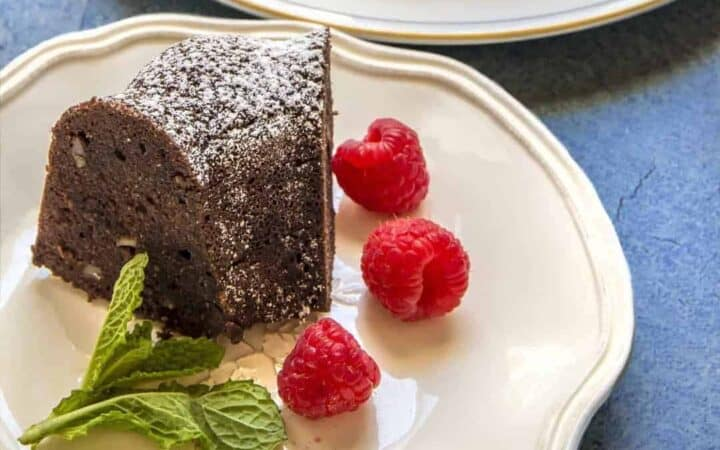 Keto Chocolate Cake on a white plate with raspberries and mint.