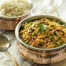 Instant Pot Kheema in small brass pot with rice at the back sideways view