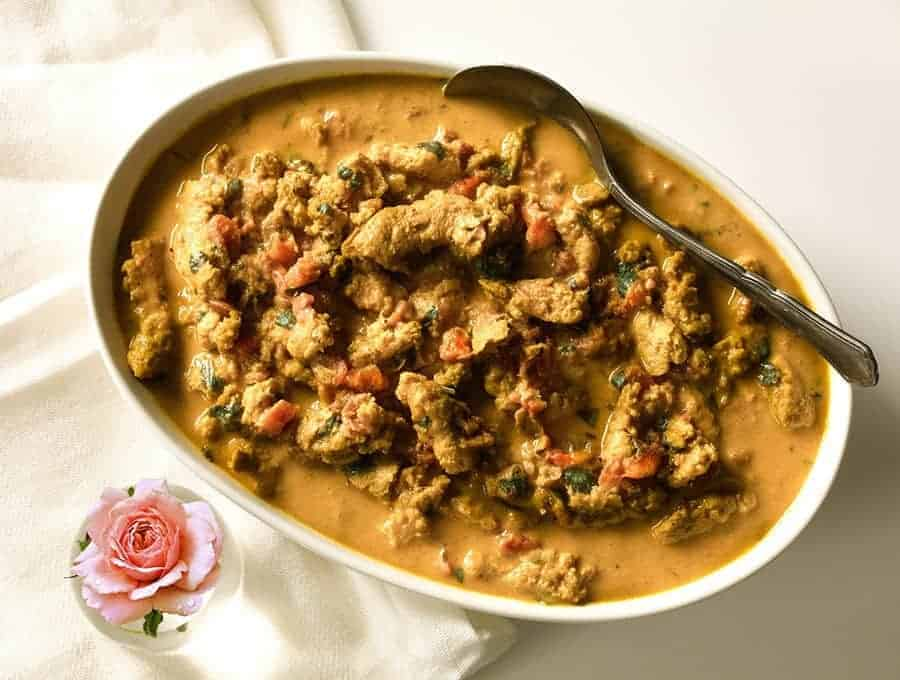 Vegetarian Butter Chicken with sauce in a white serving bowl with a spoon for serving.
