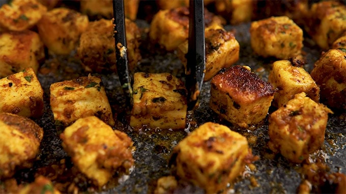 Side shot of flipping the paneer with tongs.