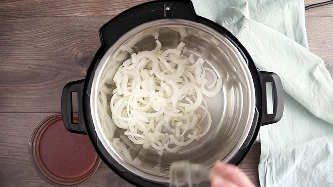 Overhead shot of a layer of onions in the bottom of the Instant Pot.