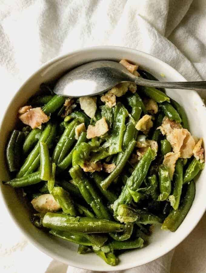 overhead shot of green beans and bacon in a white bowl on a white napkin