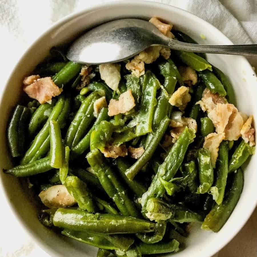A bowl of green beans and bacon.