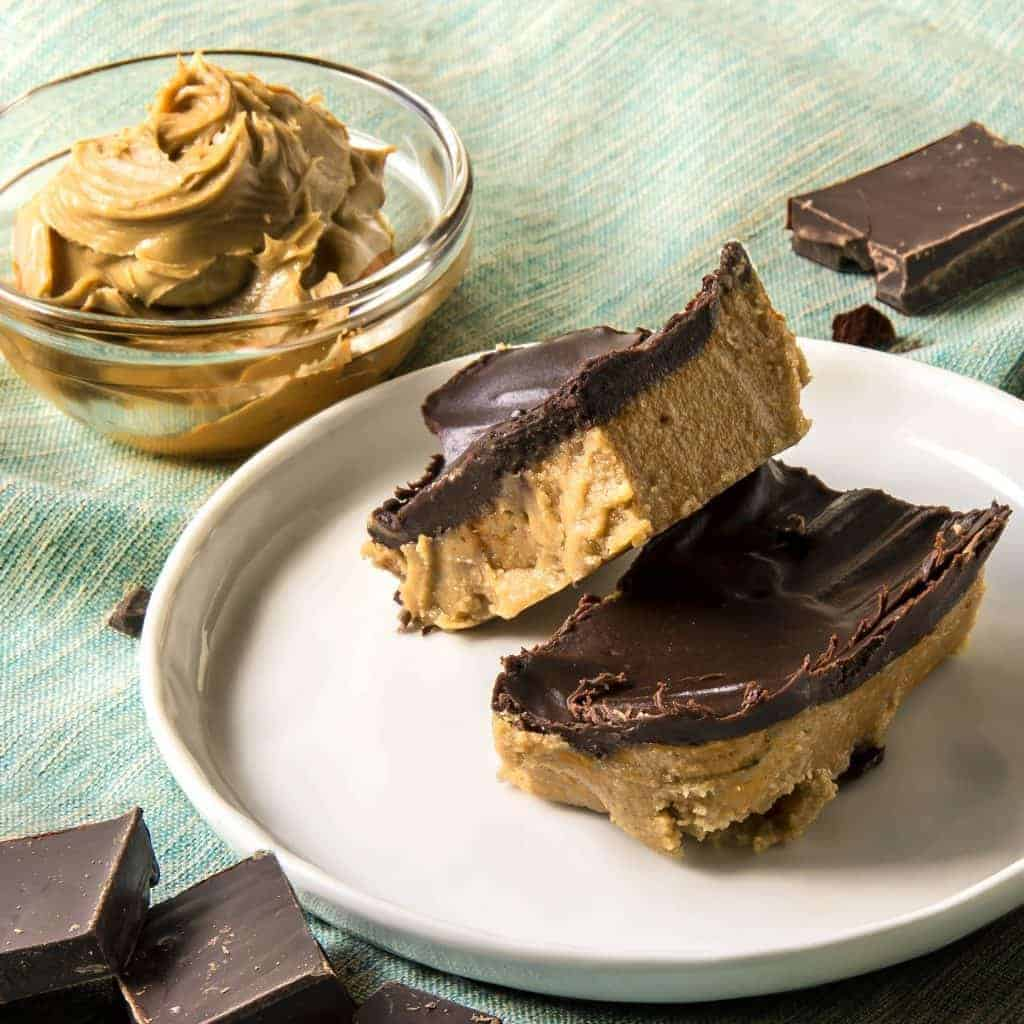 Keto dessert peanut butter bars on a plate with low sugar peanut butter in a bowl