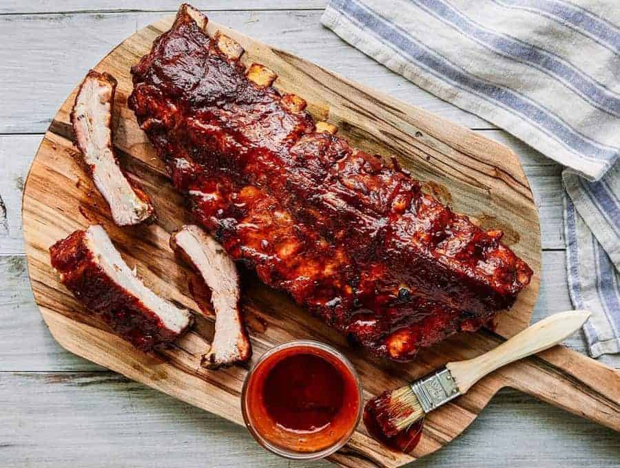 Pressure Cooker Ribs on a wooden Cutting board, with barbecue sauce on the side.