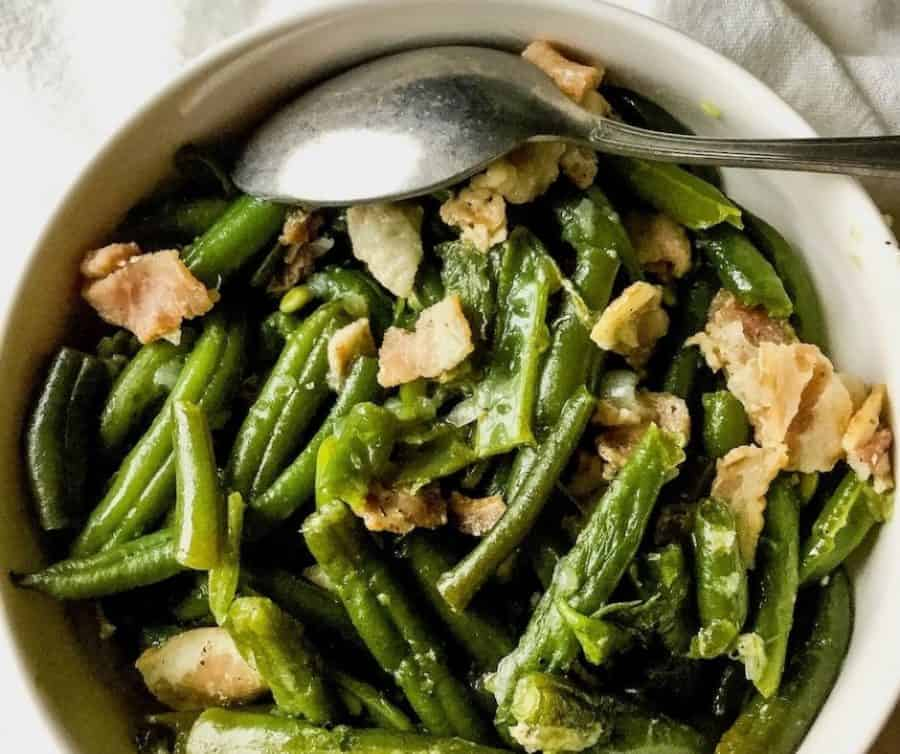 overhead view of green beans and bacon in a white bowl with a spoon