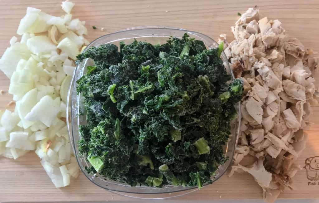 Onions, chicken, and kale for low carb chicken kale soup on wooden cutting board