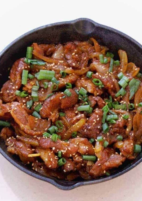 Overhead view of Dae Ji bulgogi in a cast iron pan. Savory Dae Ji Bulgogi Korean Spicy Pork cooks up flavorful and tender from your Instant Pot or Pressure cooker for a great low carb keto spicy pork dinner.