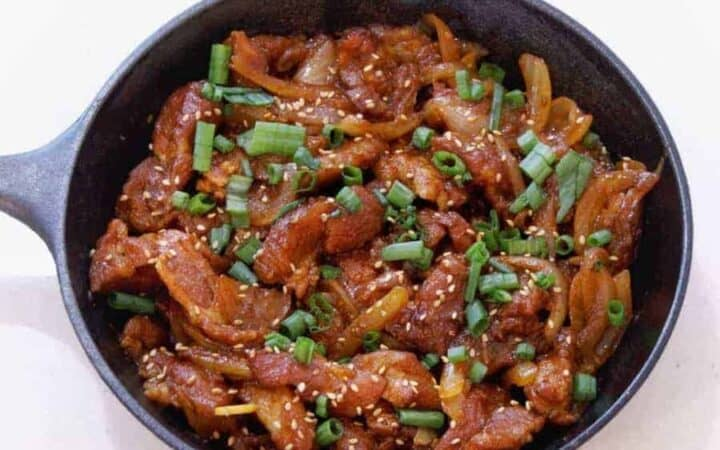 Overhead view of Dae Ji bulgogi in a cast iron pan. Savory DaeJi Bulgogi Korean Spicy Pork cooks up flavorful and tender from your Instant Pot or Pressure cooker for a great low carb keto spicy pork dinner.