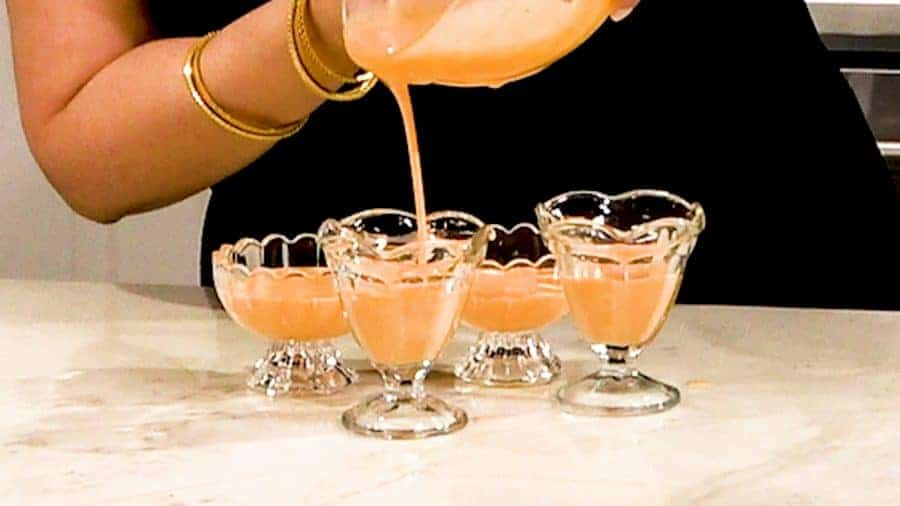 Side shot of pouring mixture into 4 ramekins.