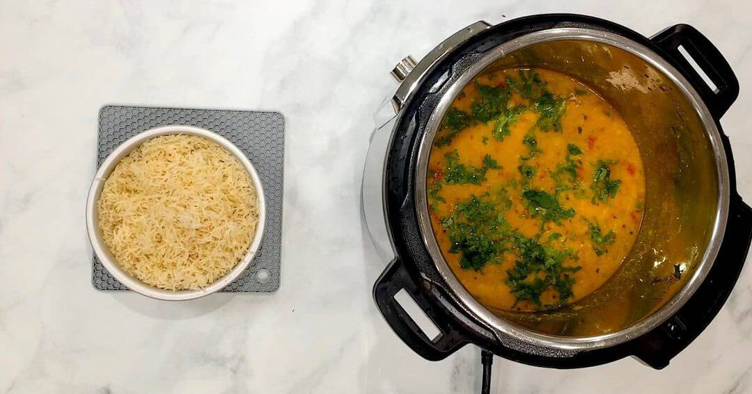 A Bowl of rice next to a pressure cooker of rice and dal.