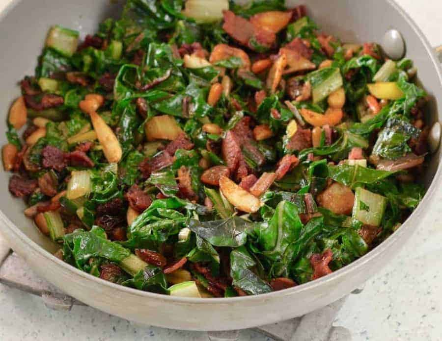 Nutty Bacon Swiss Chard bowl overhead view of a half bowl. Make a quick Nutty Bacon Swiss Chard Sauté with garlic, pine nuts, and raisins for a low carb keto side dish that dresses up any meal in less than 20 minutes.