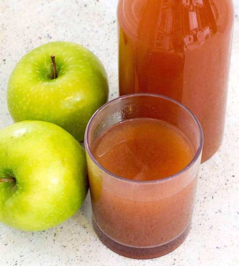 Glass of apple cider with two granny smith apples and a bottle of cider in the back. Here's how you can start with fresh apples, and end up with some of the most flavorful Mulled Apple Cider you've had—in about 30 minutes. Choose the sweetener and spices of your choice to customize this Mulled Apple cider to your taste.