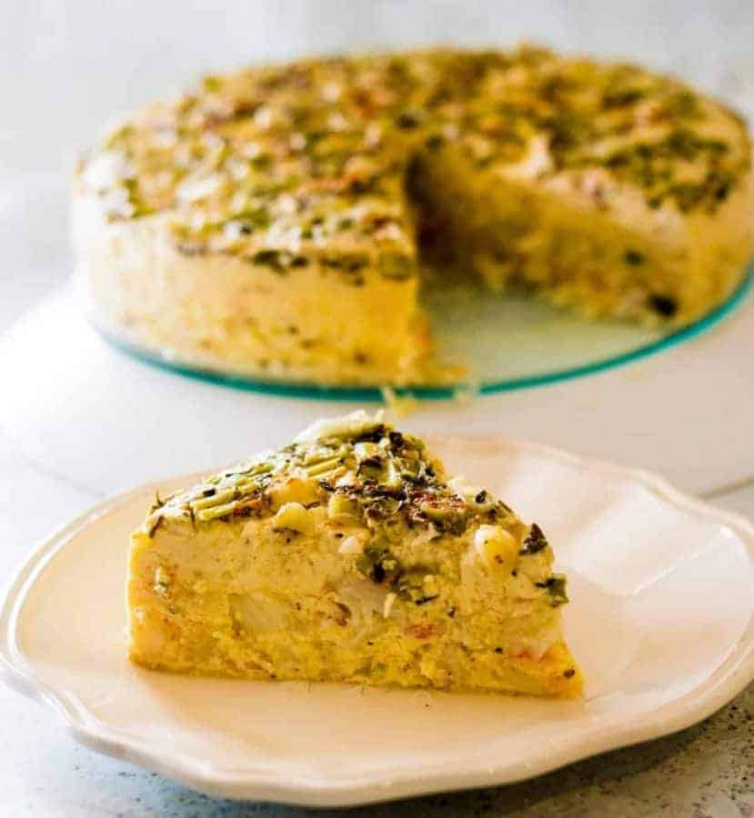 slice of crab quiche with rest of the keto crustless crab quiche in the back