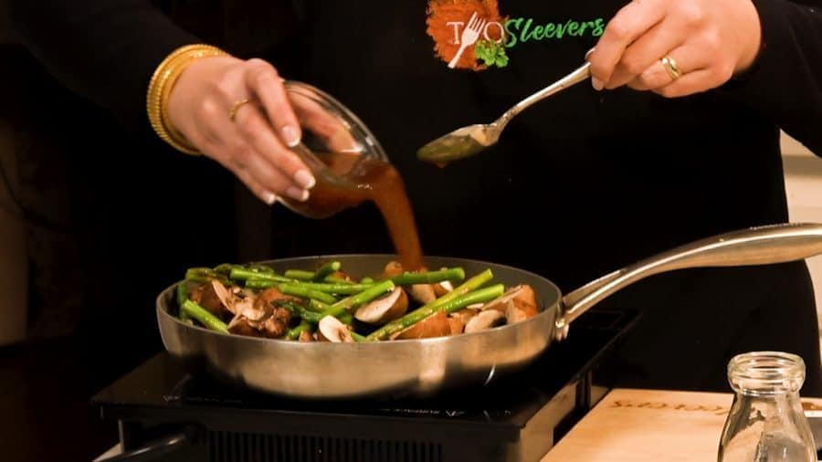 Side shot of adding the mushrooms and sauce to the pan with the asparagus.