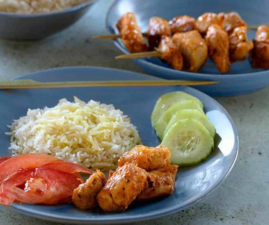 Persian Chicken Kabobs without a skewer on a blue plate with sides of cucumber, rice, and fresh tomato