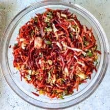 Beets, carrots, and cabbage combine to make a quick Indian raw vegetable salad that is as beautiful as it is nutritious. Add your favorite raw vegetables to this vegan salad that makes a great side dish for your meals.