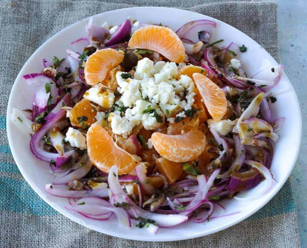 overhead shot of pickled red onion and orange salad on a white plate with feta cheese crumbles on top