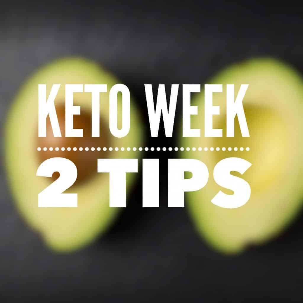 Avocado split open against black background keto Week 2 tips for getting started on keto