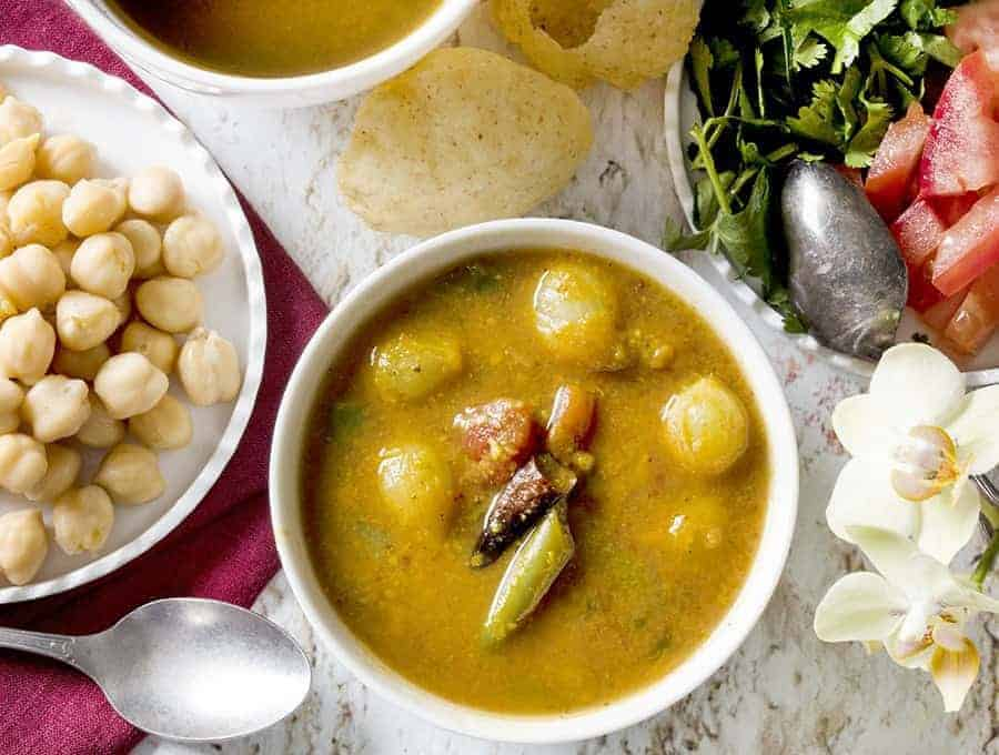 Instant Pot Sambar overhadd shot with sambar in white bowl along with pearl onions
