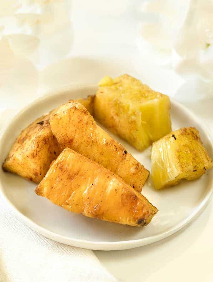 Brazilian Grilled Pineapple spears in a white plate, sideways view