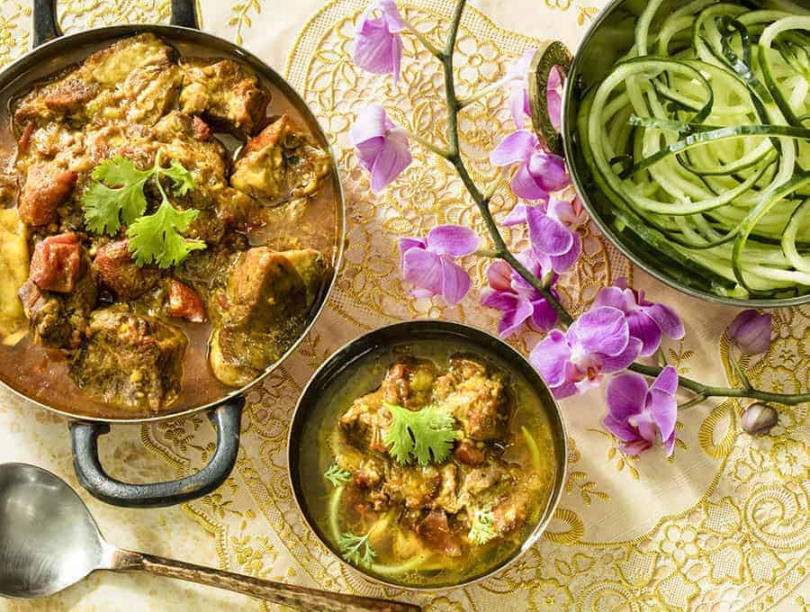 Indian Curry in a large sauce pot with a side dish of zoodles and a spoon