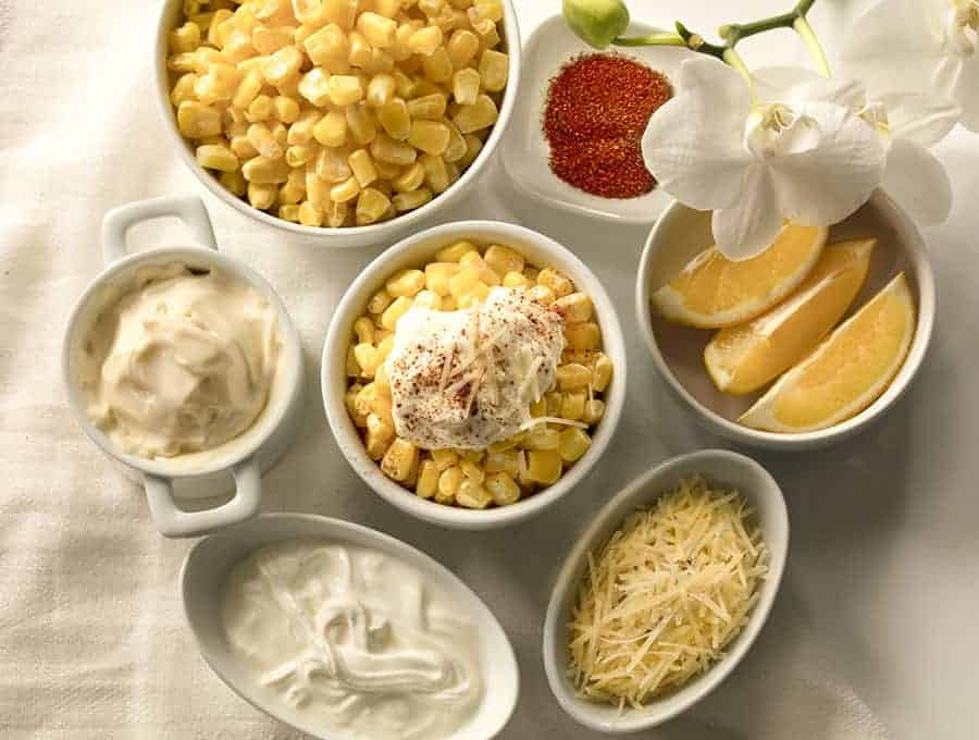 Bowls filled with different types of food on a table including lemons, cheese, dips and corn.
