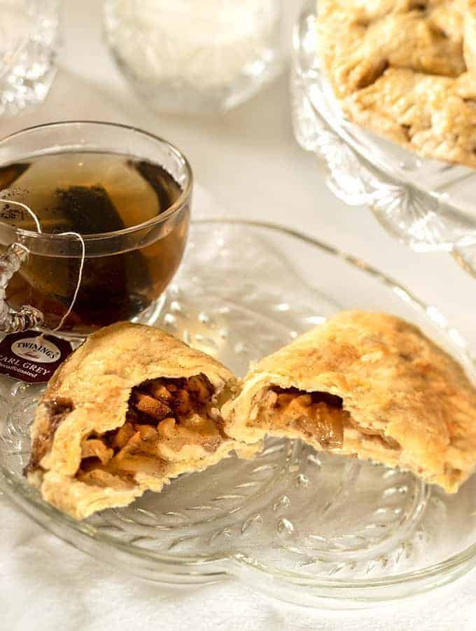 Apple Hand Pies on a Glass Platter with a cup of Tea