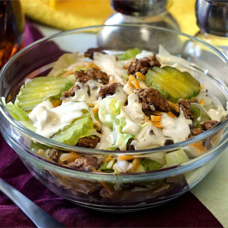 big mac salad low carb hamburger salad in a glass bowl with pickles and dressing on top