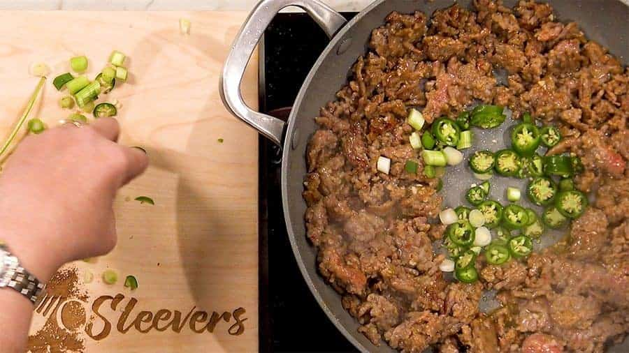 Overhead shot of adding green chilis to center of pan with the ground pork.