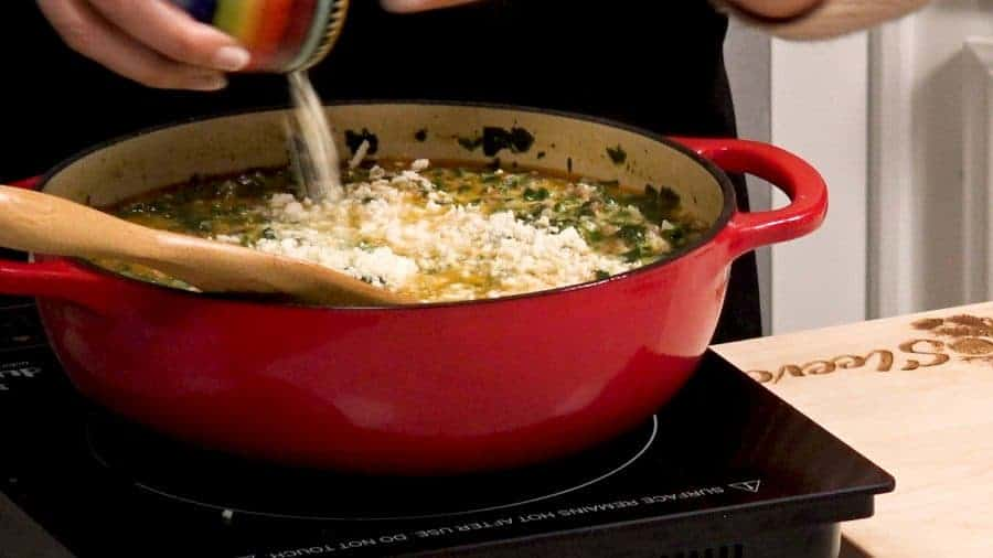 Pouring cream and cheese into a red pot full of soup.