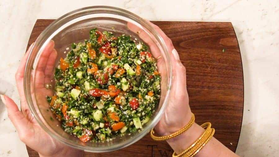overhead view of hands holding a bowl of keto tabouleh, ready to eat.
