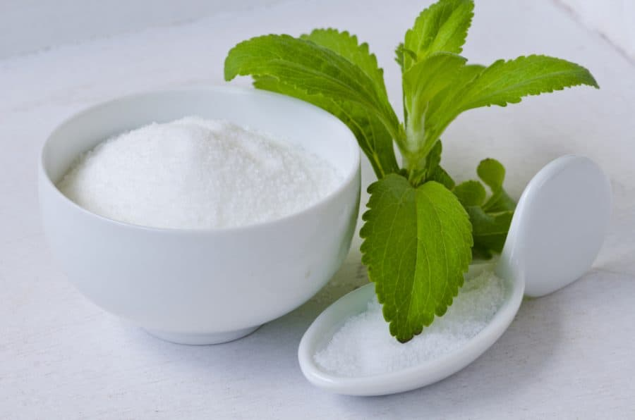 A bowl of Stevia Sweetener with Stevia leaves beside it.