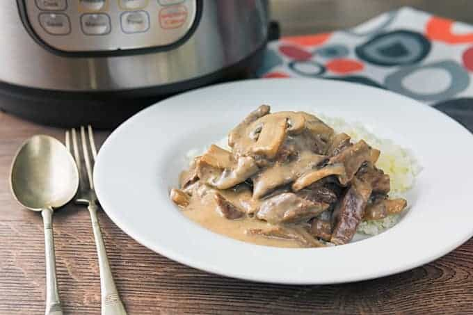 Instant Pot beef stroganoff with gravy on a white plate, with a fork and spoon on the side.