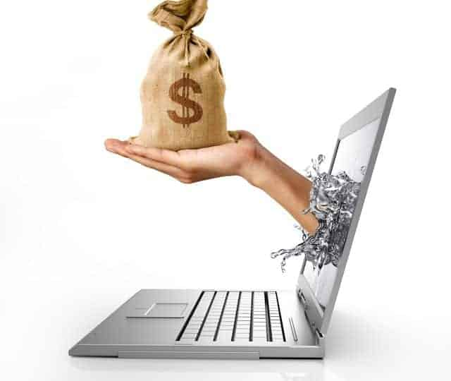 Man's hands, splashing out from a computer laptop screen, holding a bag of US Dollars money on it. On white background, with clipping path included.