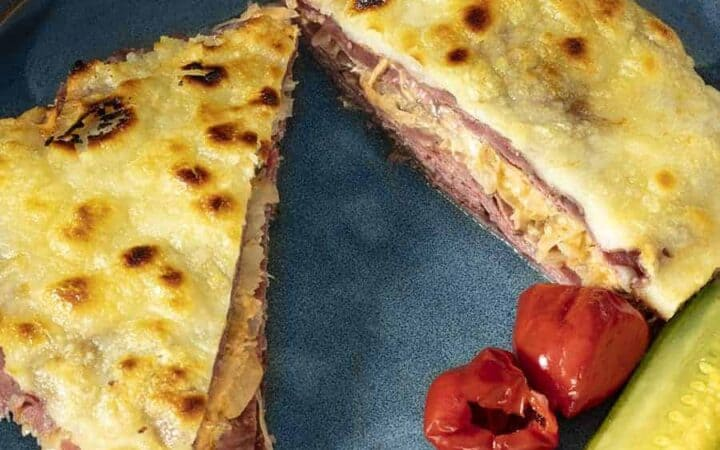 Baked reuben casserole cut into triangles with pickles