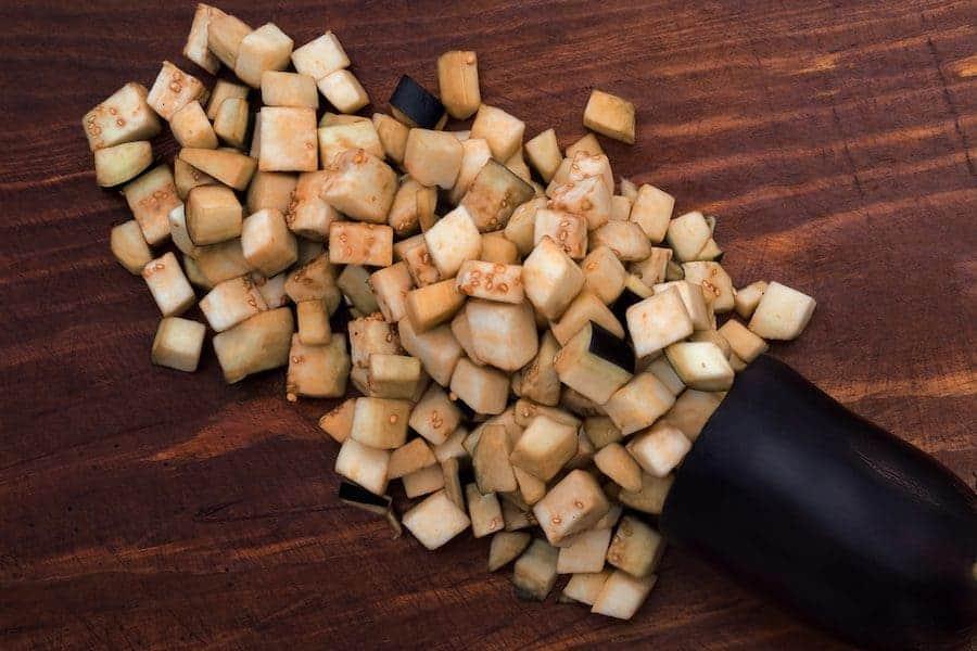 diced eggplant on a dark wooden cutting board