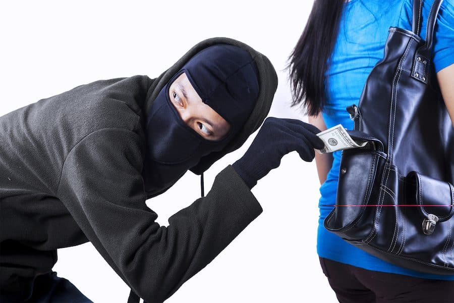 Thief stealing money from handbag of a woman